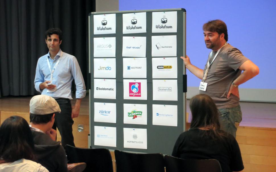 Die Organisatoren mit der Sponsoren-Wall beim Barcamp Schweiz