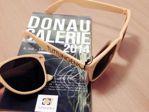 Die gelbe Brille mit dem Flyer der Donaugalerie